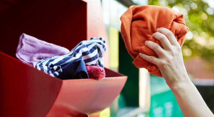 Garments being placed in clothing recycling bin.